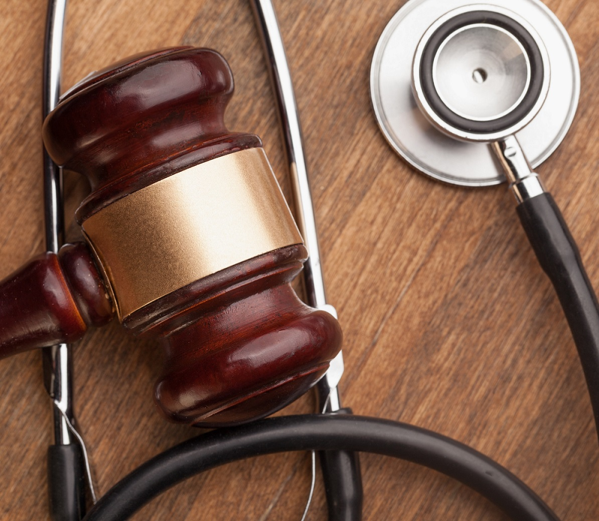 A judge's gavel with a stethoscope laying on a table