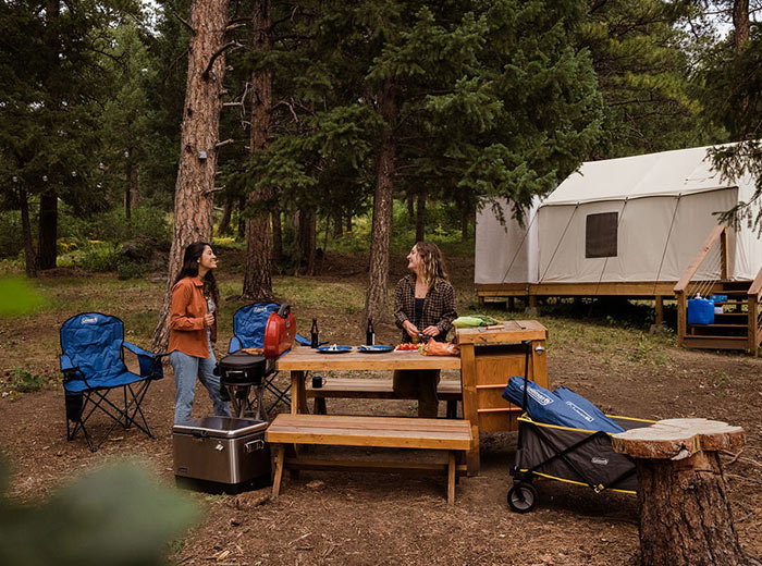 A camping stove and some dishes on top of a picnic bench.