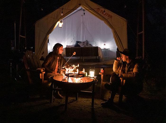 Coals blaze on fire inside a metal camping fire pit.