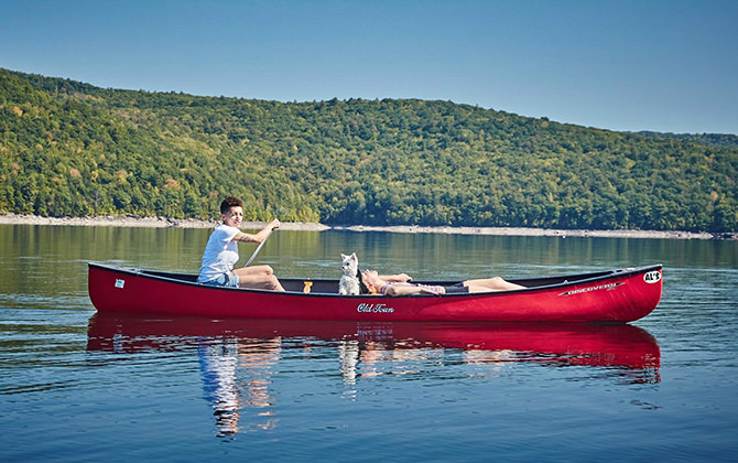 Two people and a small white dog in a red kayak, paddling on a beautiful, secluded lake