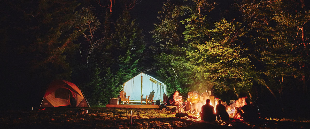 Night time shot of people around a campfire with a Tentrr tent