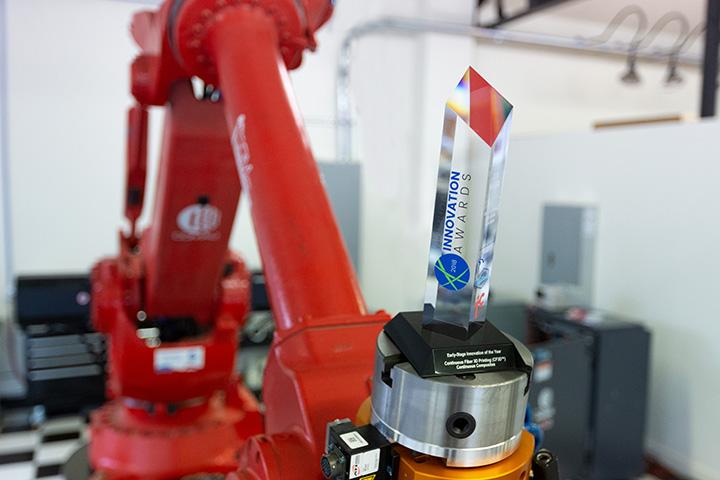 Comau robotic arm holding award