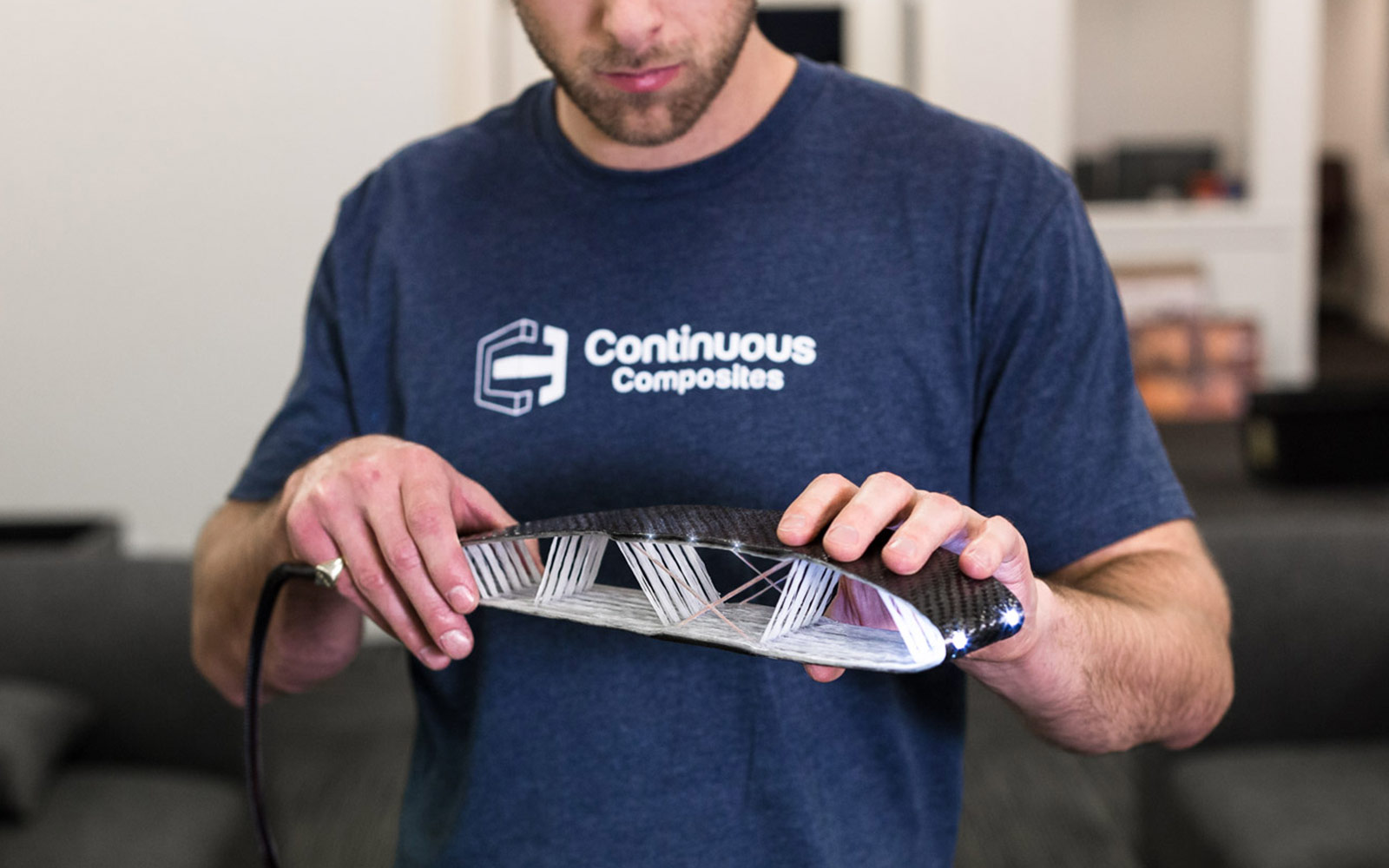 Team member holding embedded functionality airfoil with copper wire and fiber optics.