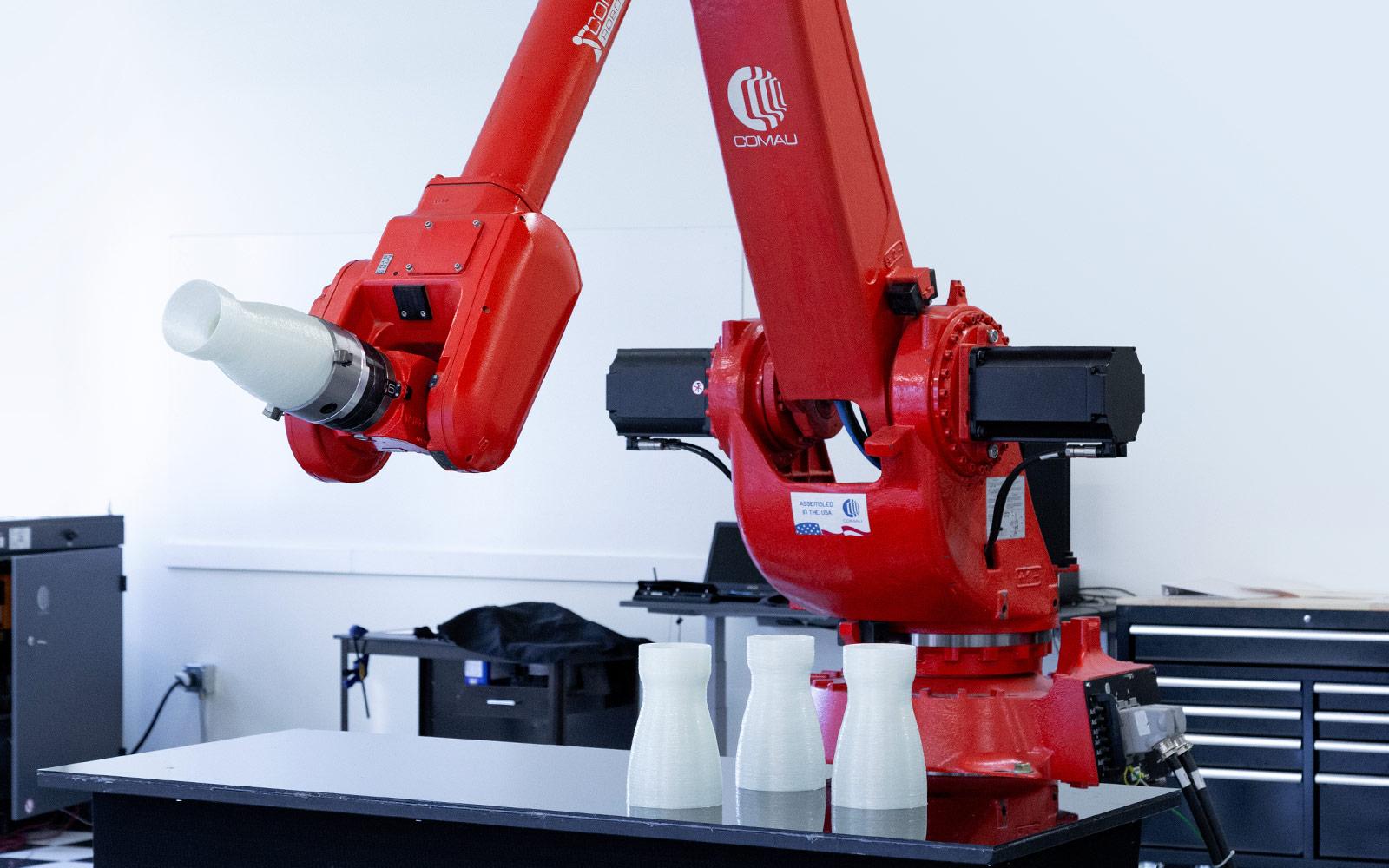 NJ130 Comau robot holding fiberglass de laval nozzle.