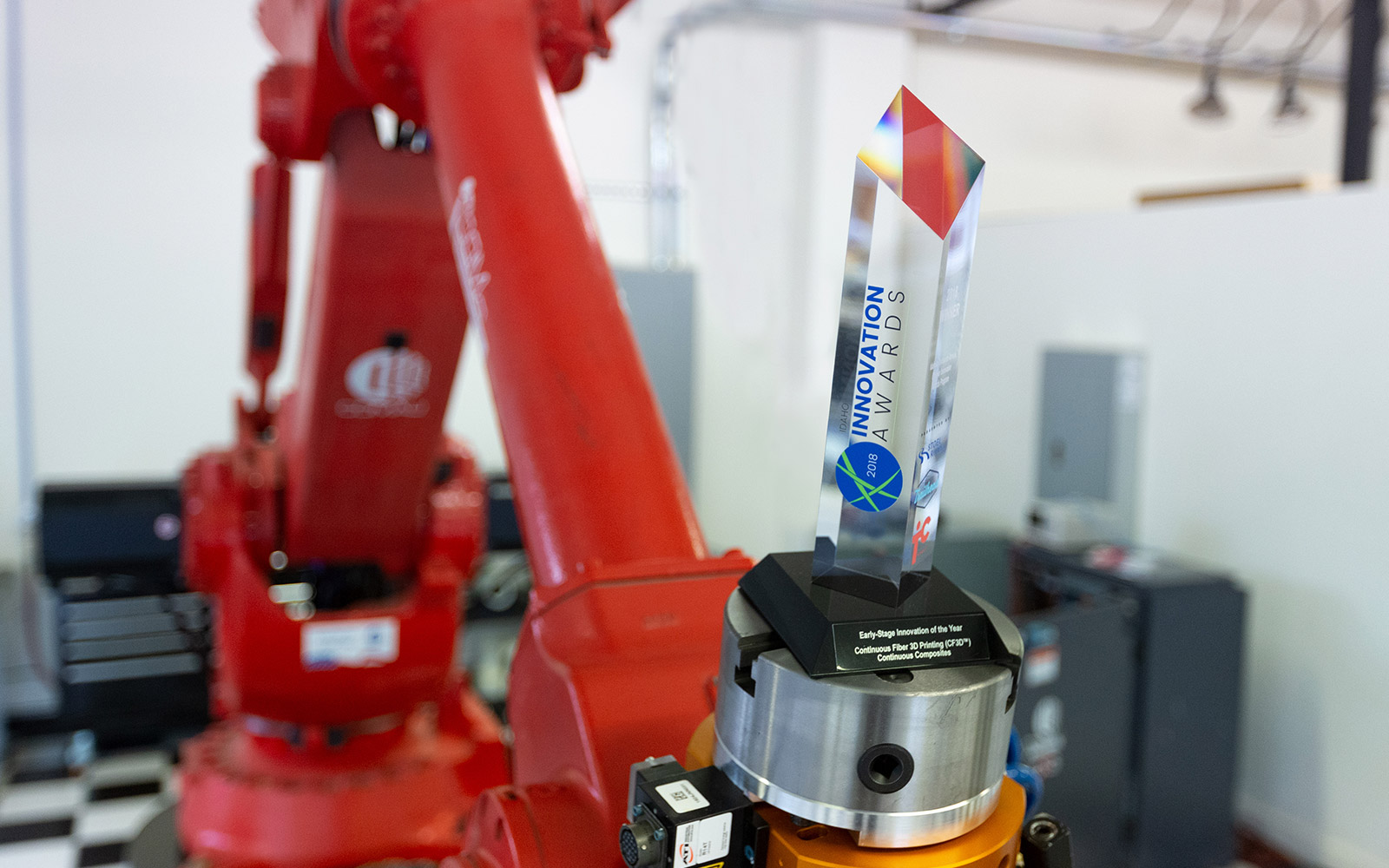 Comau robotic arm holding award