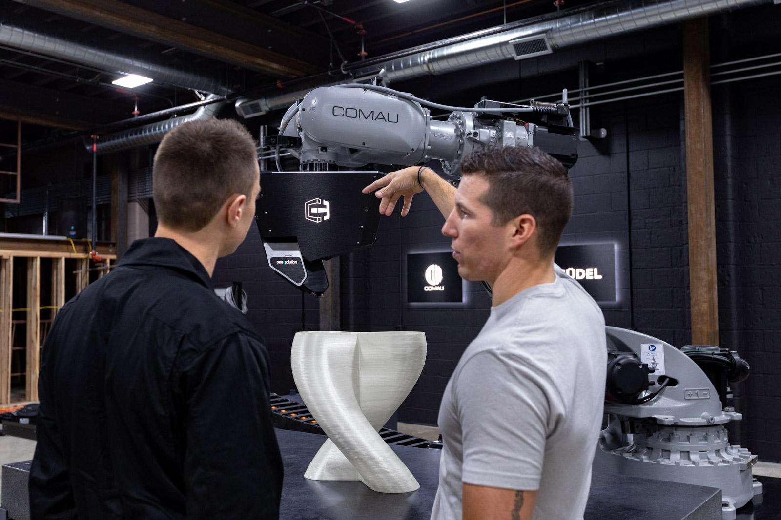 CEO, Tyler Alvarado talking with Lead R&D Tech, Tyler Wilson in front of print head