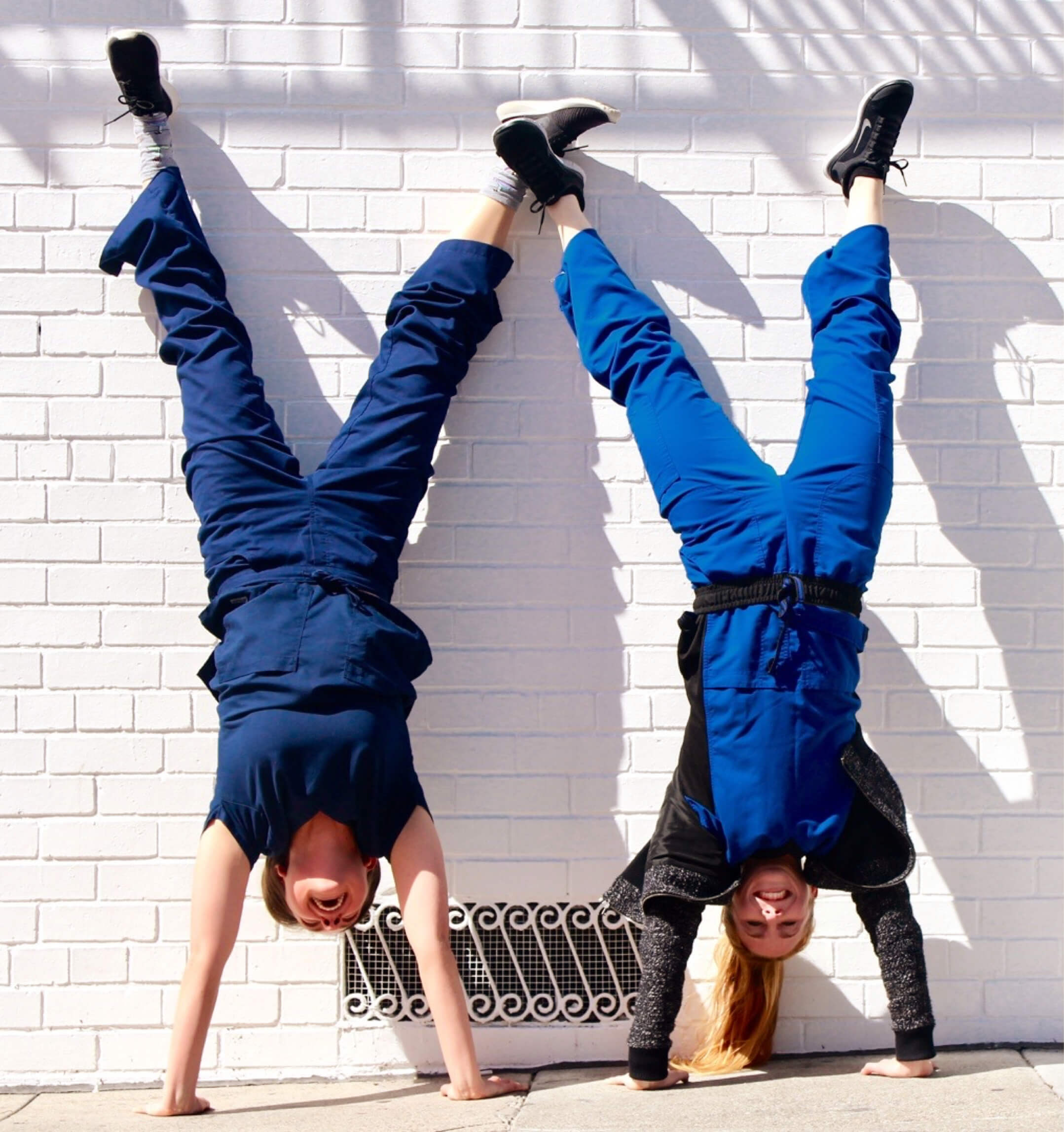 two trusted health nurses doing handstands against a wall