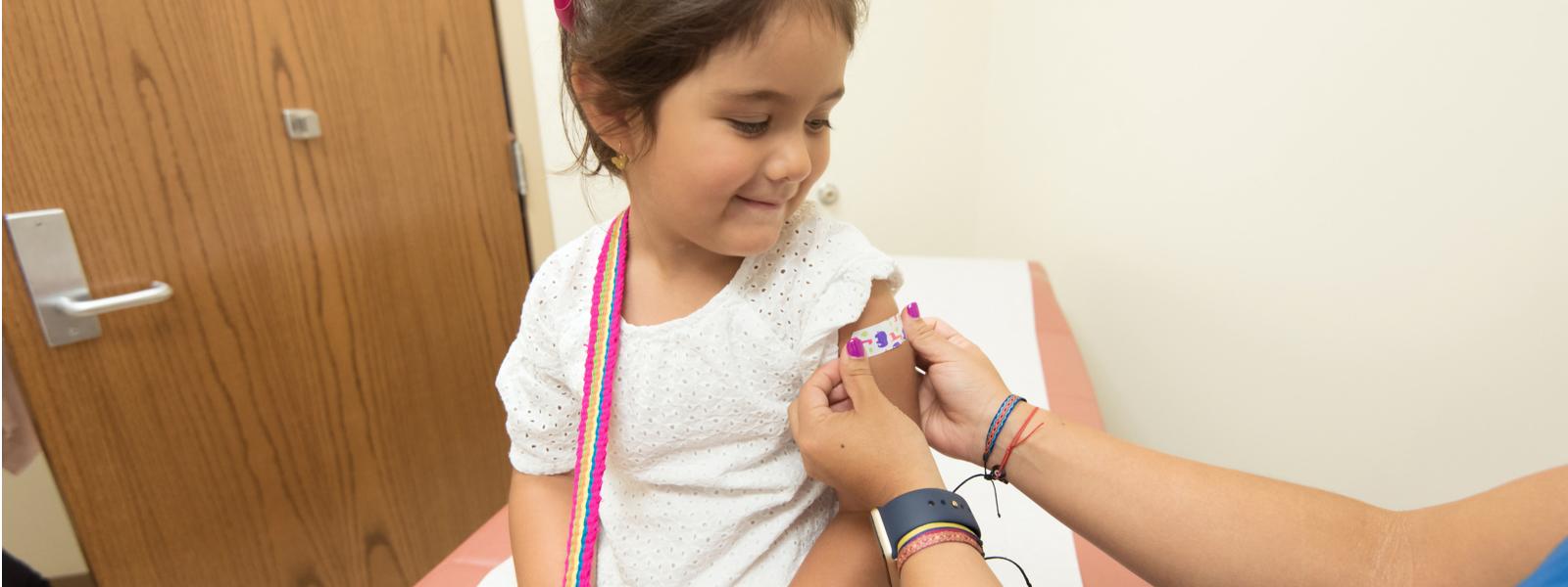 nurse puts bandaid on little girl new grad nursing skills
