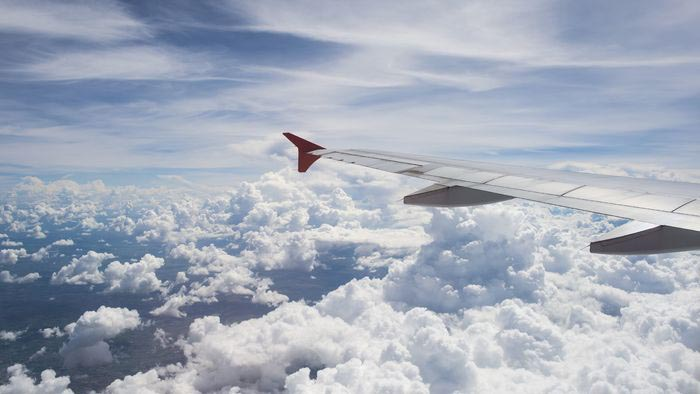 An airplane wing over a cloudy blue sky - the view from an airplane window.