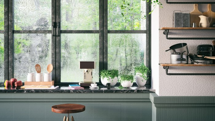 A kitchen bench with windows facing out to rain.