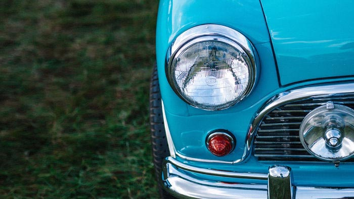 A retro sky blue car headlight detail against green grass.