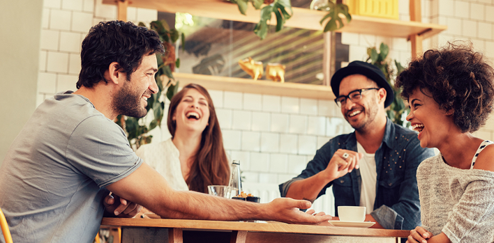 Four people sitting at a cafe table talking and laughing.