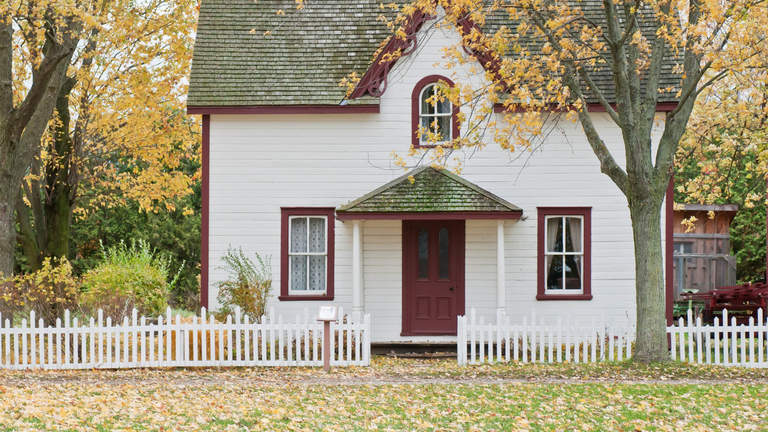 A home painted white with a red door in autumn.