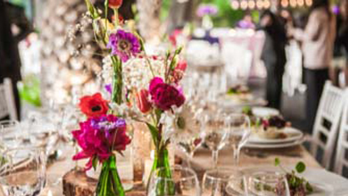 A wedding table setting with pink and purple flowers.