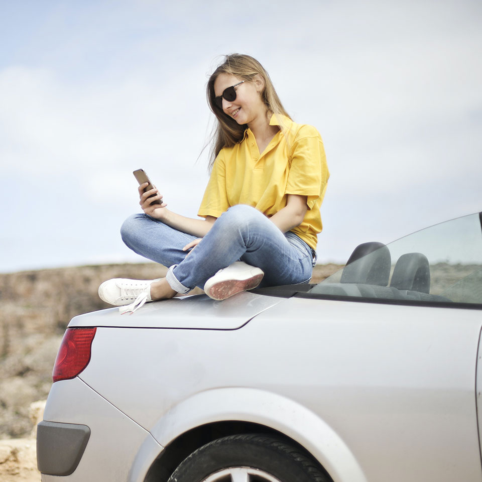 A woman on a car looking at her phone