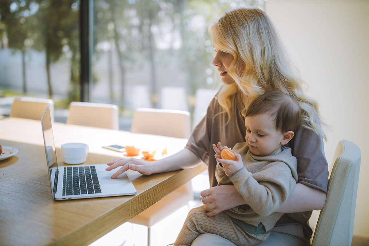 Woman with her child looking at a laptop