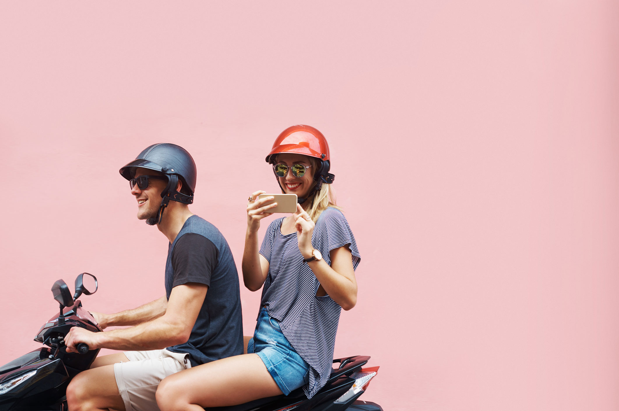 couple on scooter travelling pink background