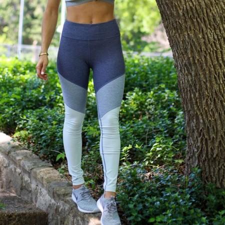 woman in athletic leggings balancing on stone walkway
