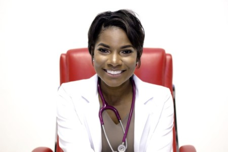 Nurse Boss tanisha terry sitting in red chair ready to see a patient
