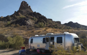 RV parked in desert in front of small mount nomadic nurse
