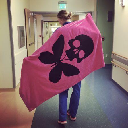 nurse erin kilroy in unit hallway holding up designed blanket