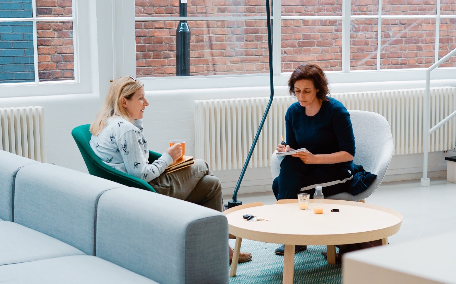 two woman sit on sofa chairs inside home studying