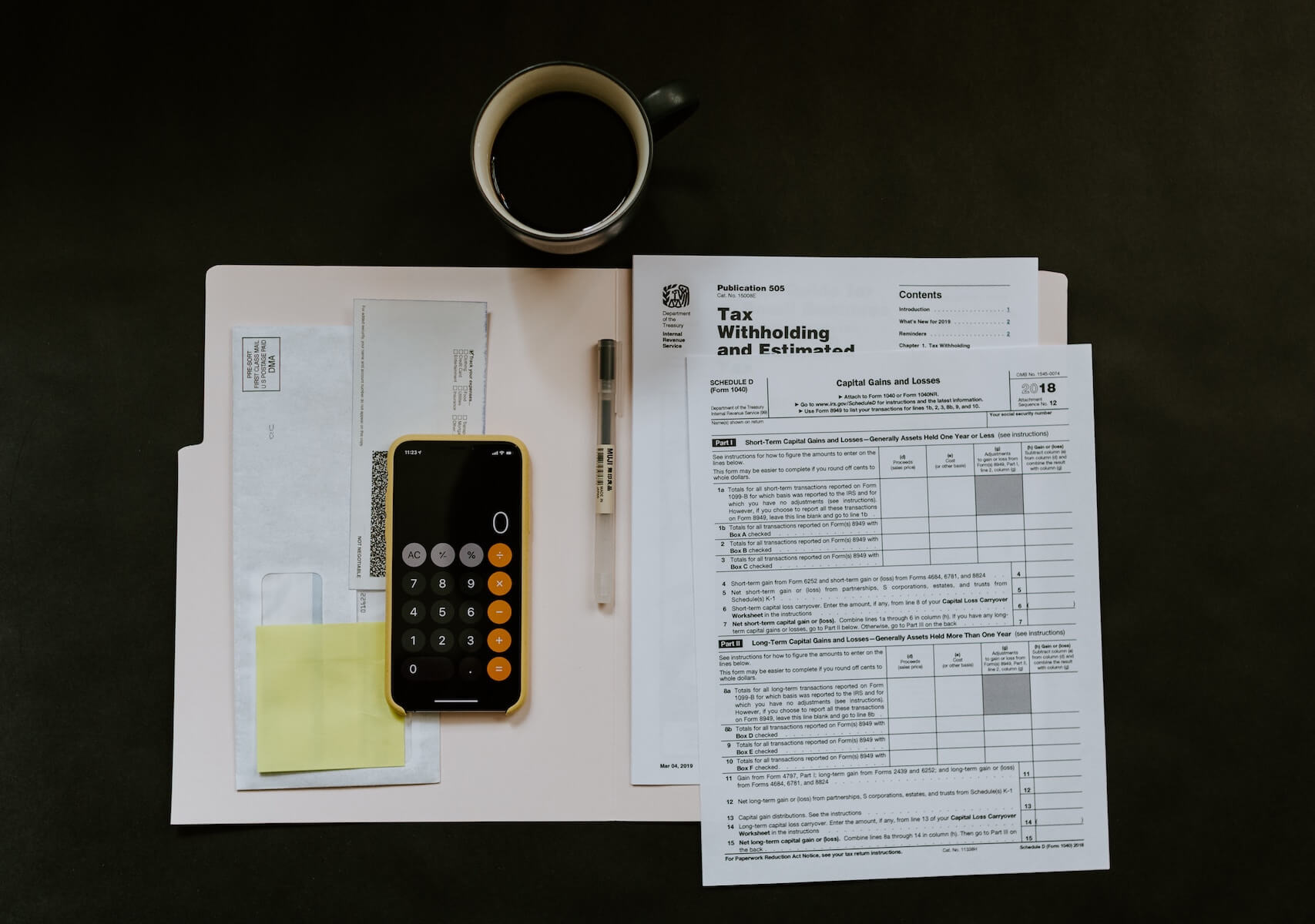 tax papers and coffee on black desk travel nurse taxes