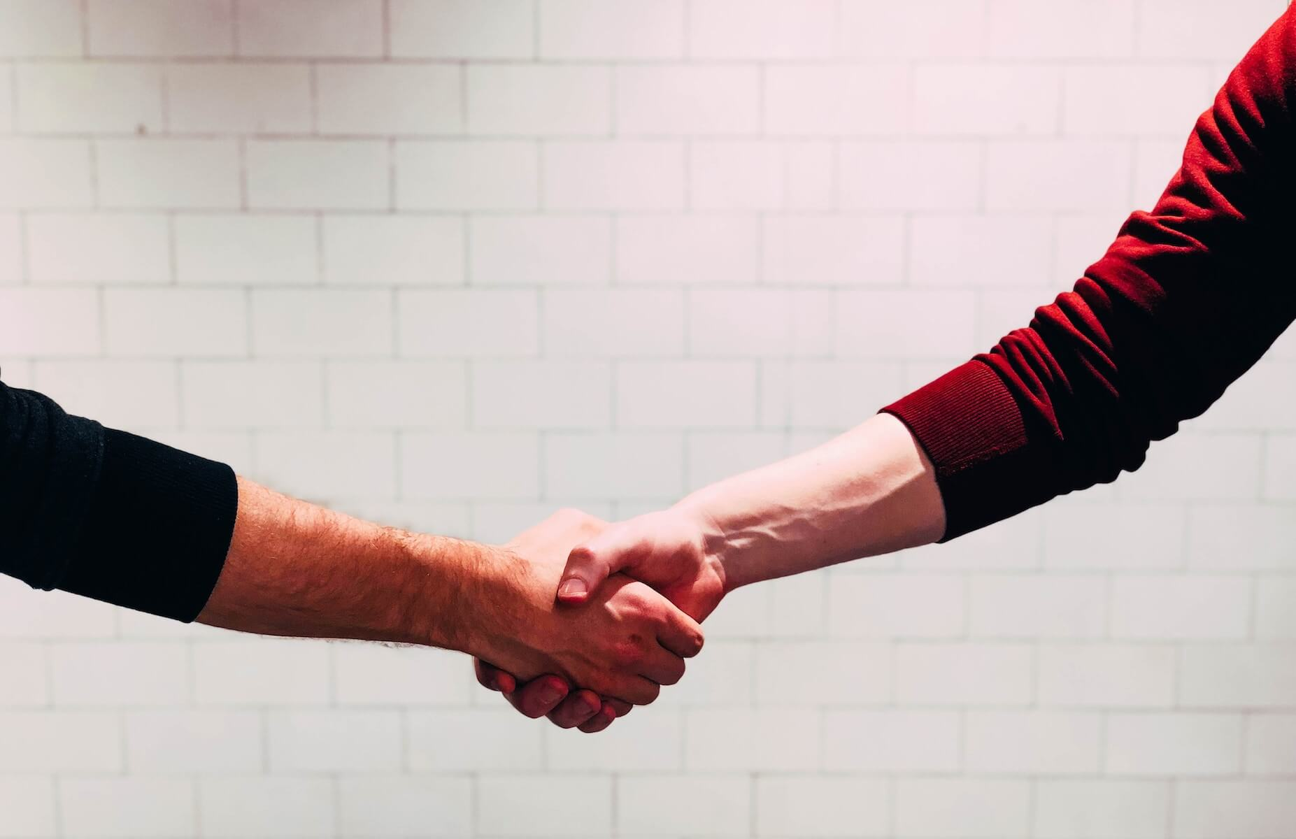 two men shaking hands negotiating travel nurse contract