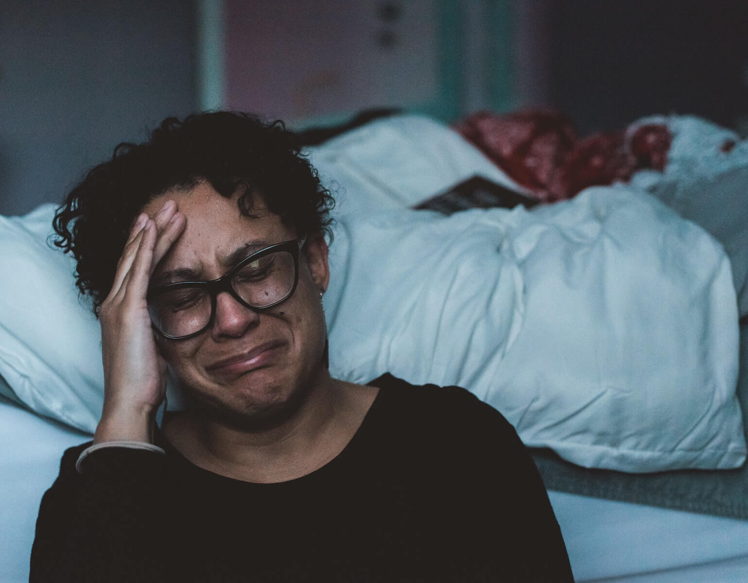 woman sitting in bedroom hand to face crying covid19 nursing moral injury