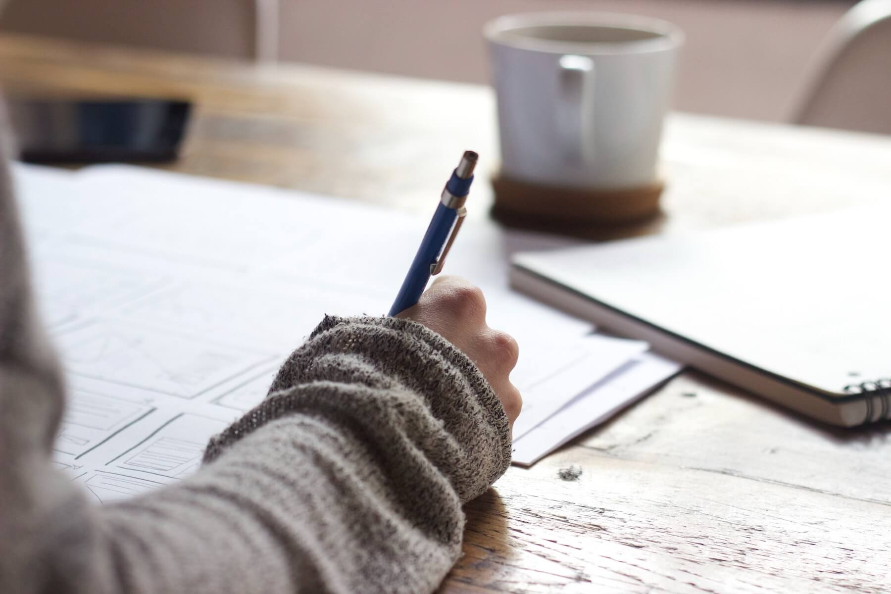 woman holding pencil sitting at cafe table with coffee and writing notes studying new grad nurse nursing