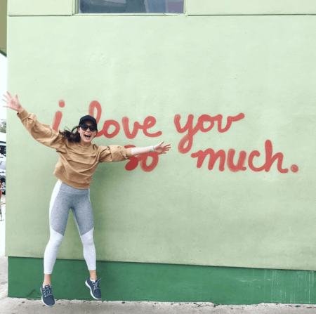 chelsea rofles nurse jumping in front of wall that says i love you so much