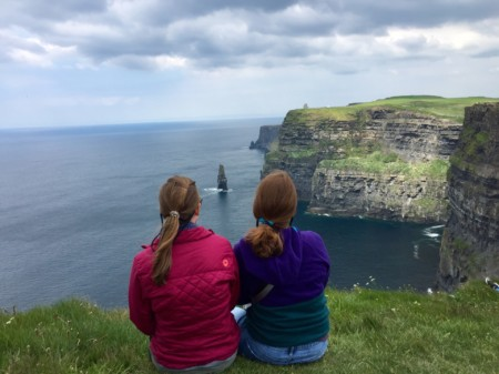 travel nurse duo watching over ocean on grassy cliffs