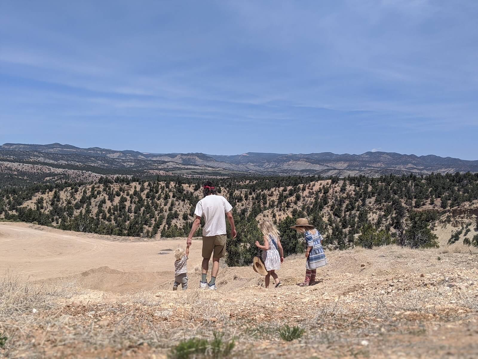 Russ Mortland RN and three kids hiking on dirt trail with trees in the background travel nursing in an RV