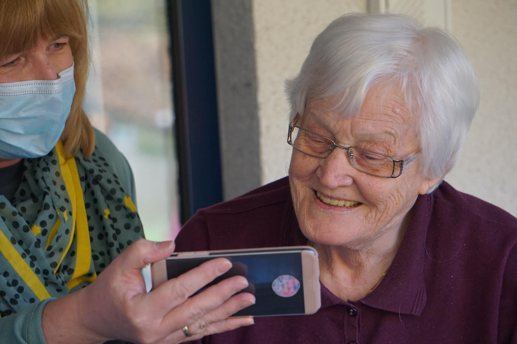 home health nurse with mask on shows elderly woman something on her phone home health nursing