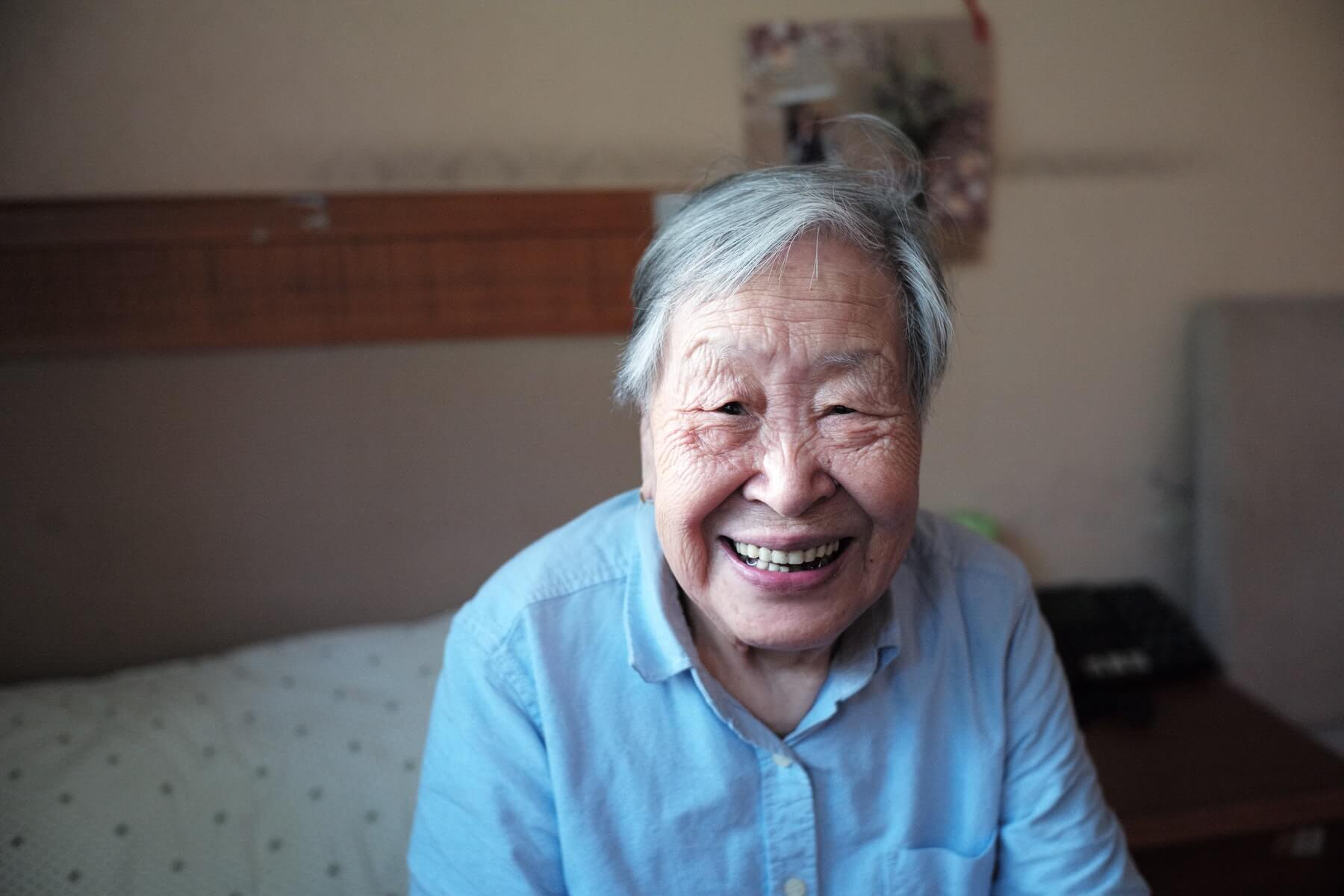 elderly woman sitting on bed and smiling into camera