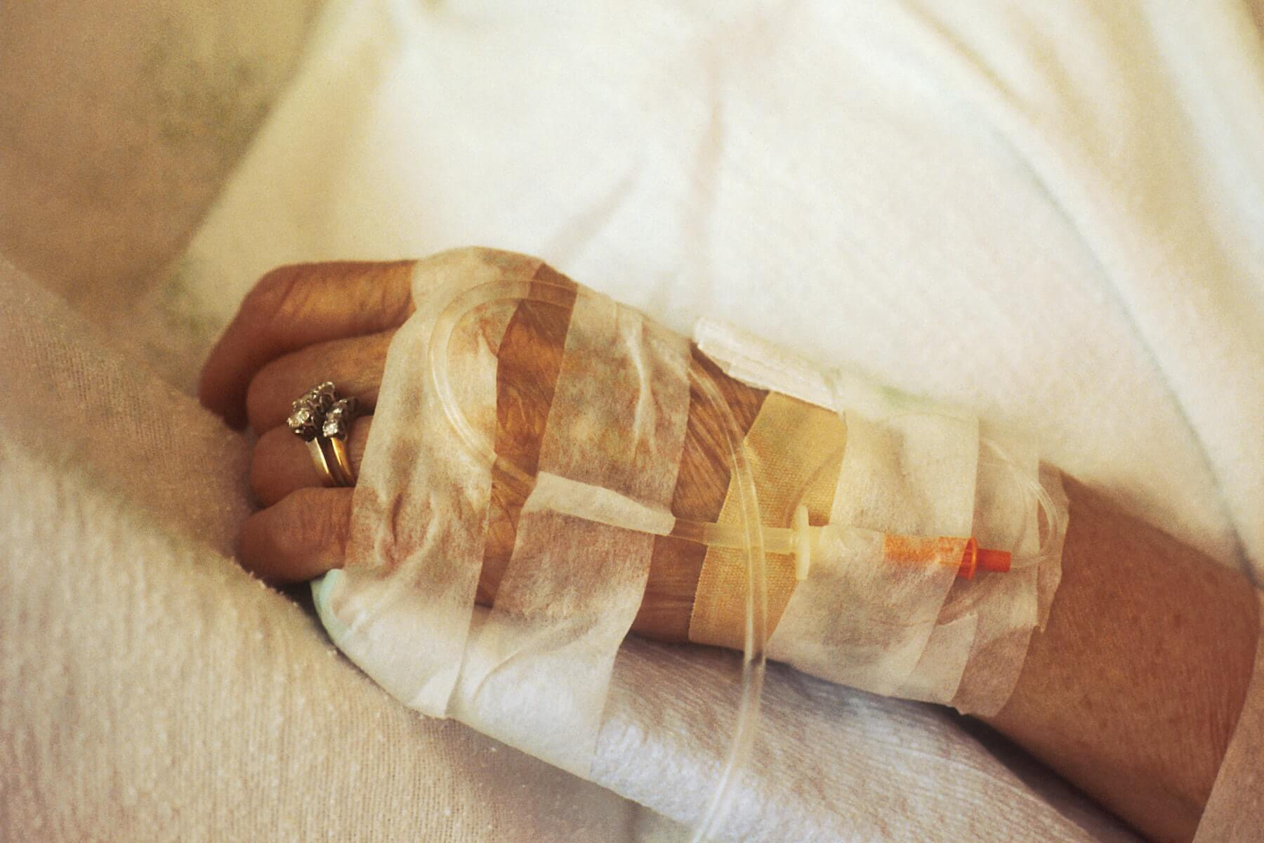 hand of old woman with IV drop attached and wedding ring on finger laying on side of bed hospice nursing