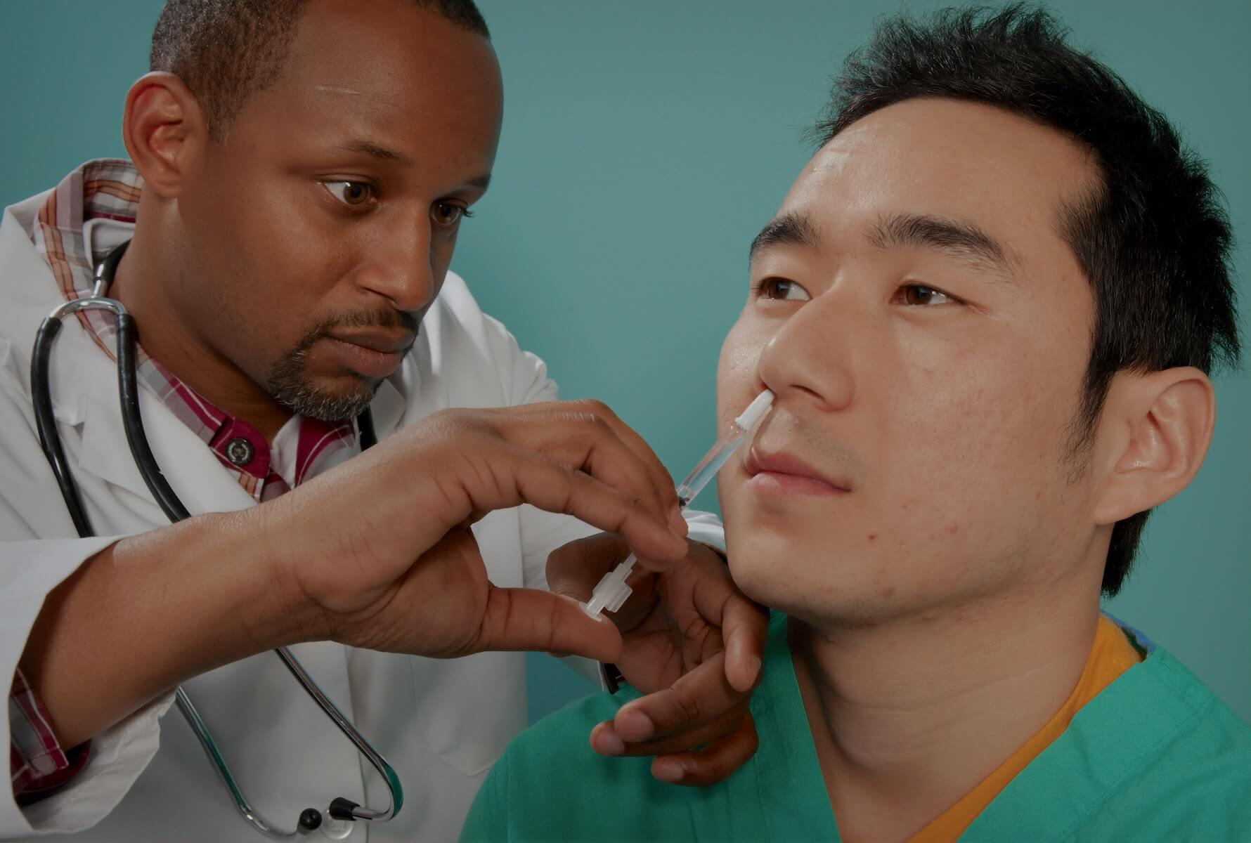 nurse practitioner gives vaccine to man on the right through is nasal cavity FNP