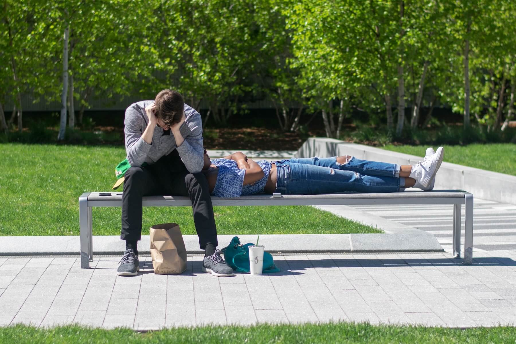 two people siting on bench one laying in the other lap and one with his head down psychiatric nurse practitioner mental health