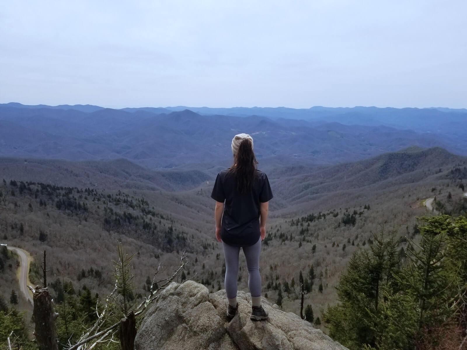 woman standing on cliff overlooking mountainous valley wilderness nursing