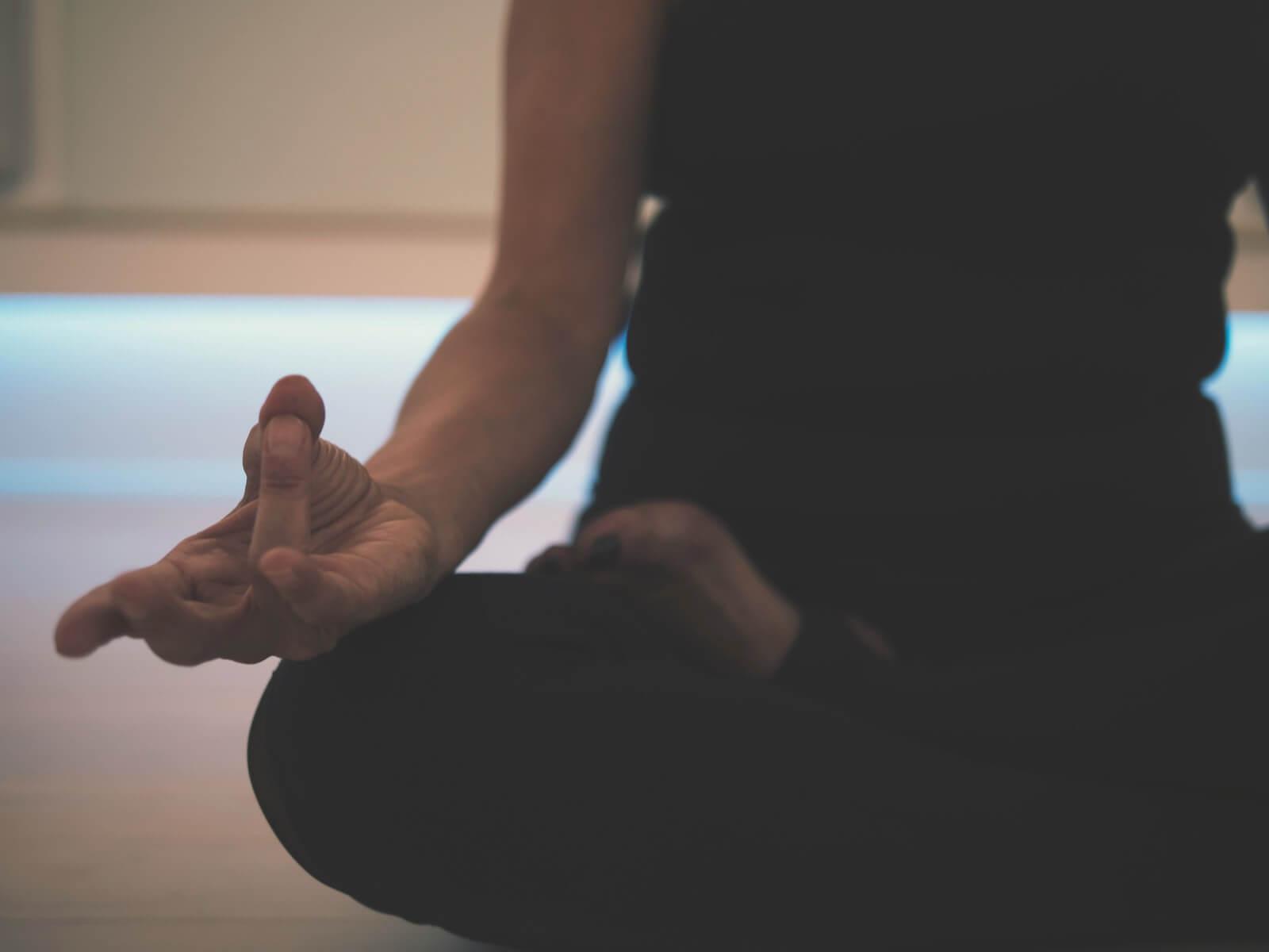 woman sitting on yoga mat meditating nurse wellness meditation