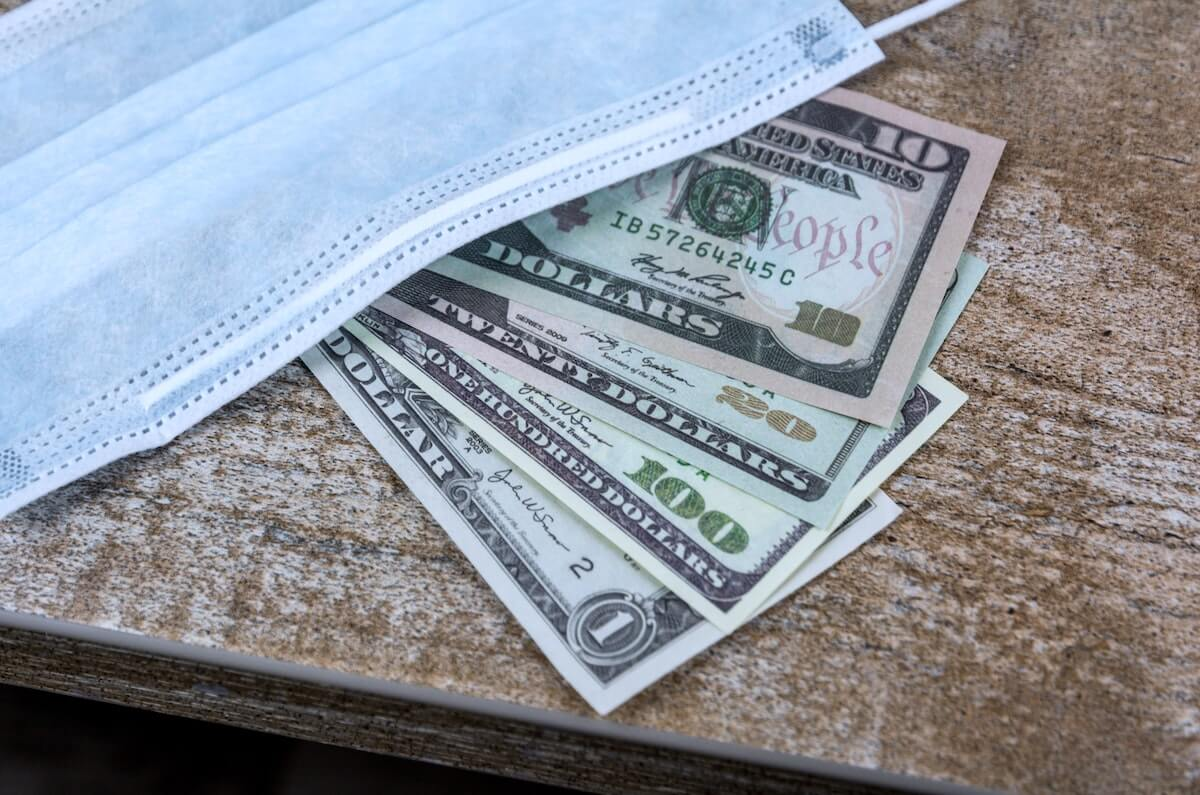 surgical mask laying on top of US money on a table do nurses make a lot of money travel nursing