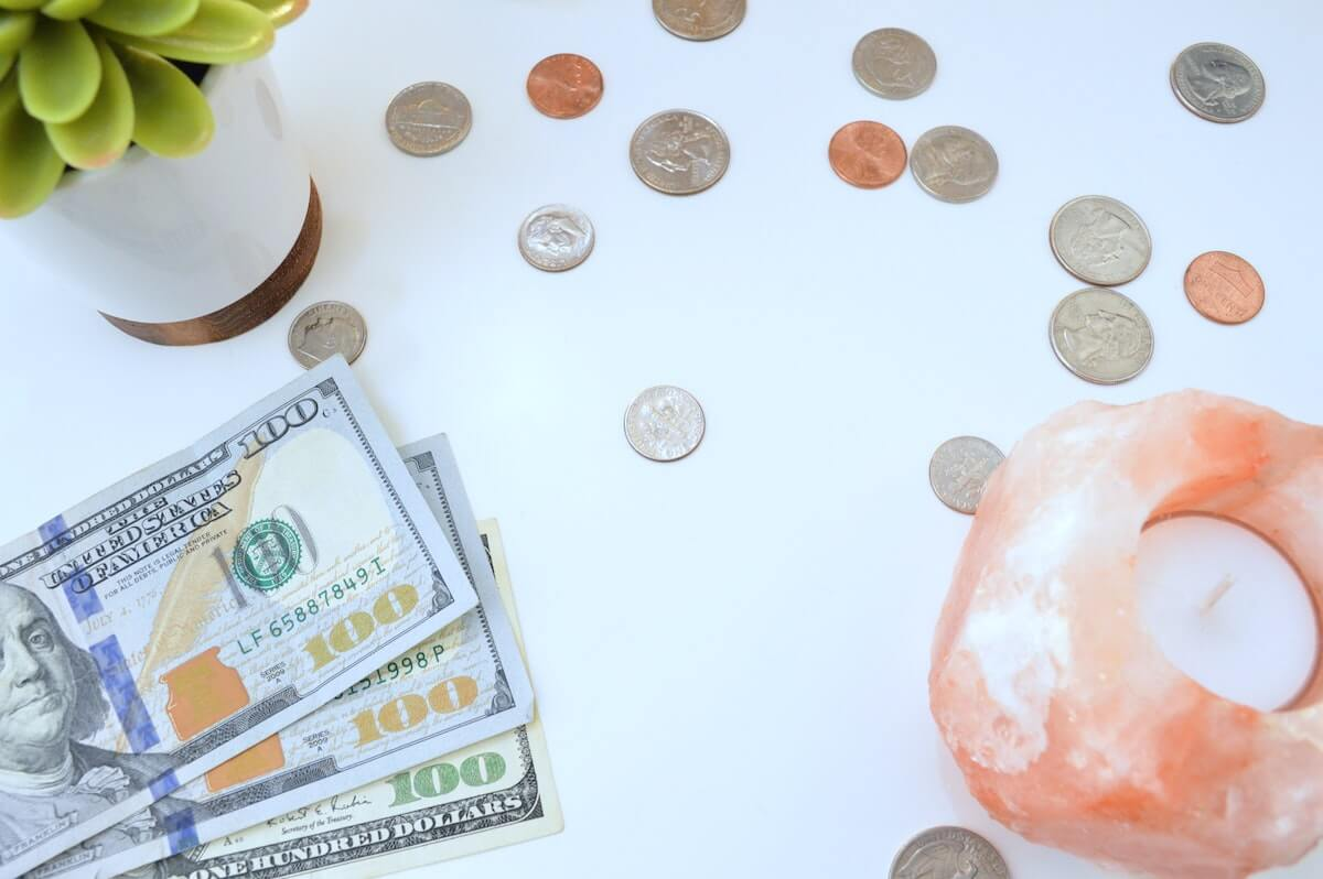US bills and coins lying on table next to succulent and candle do nurses make a lot of money