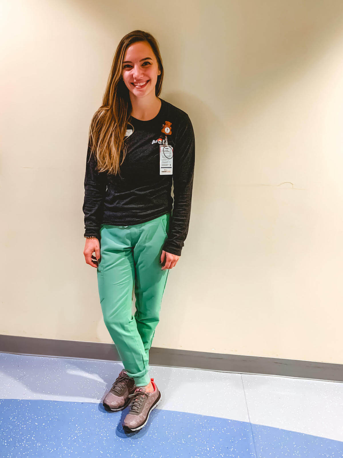 nurse ashley rn posing against wall showing off new skechers nursing shoes for nurses