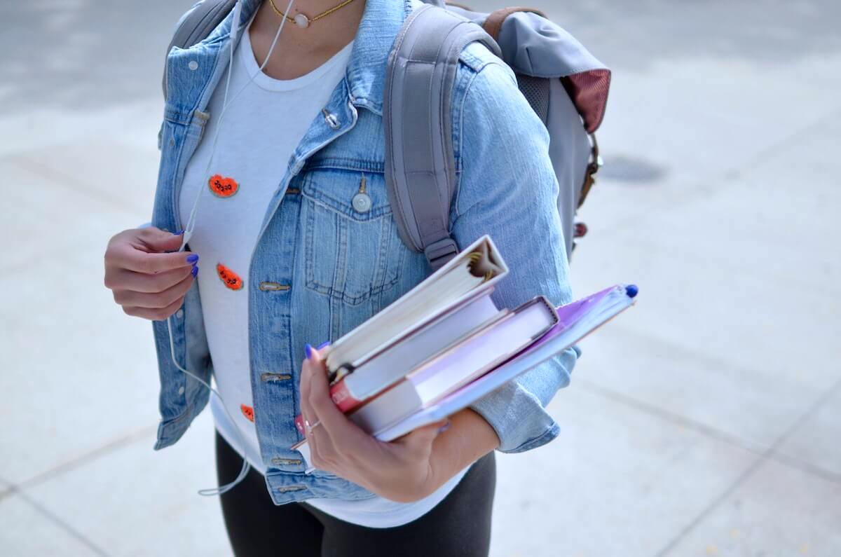 female student carrying books listening to headphones paying of nursing school debt