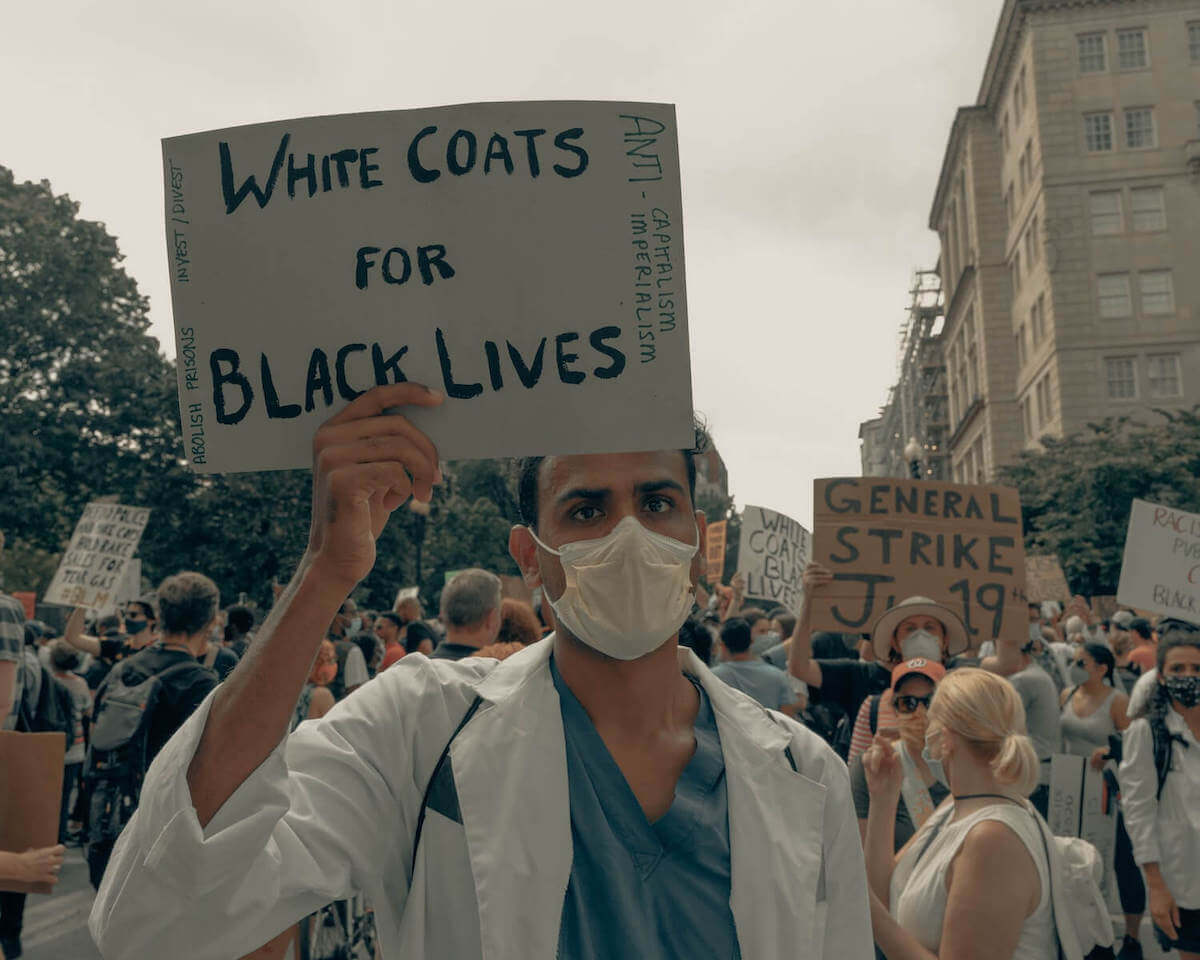 man at BLM protest holding white coats for black lives sign racial bias in healthcare healthcare disparity