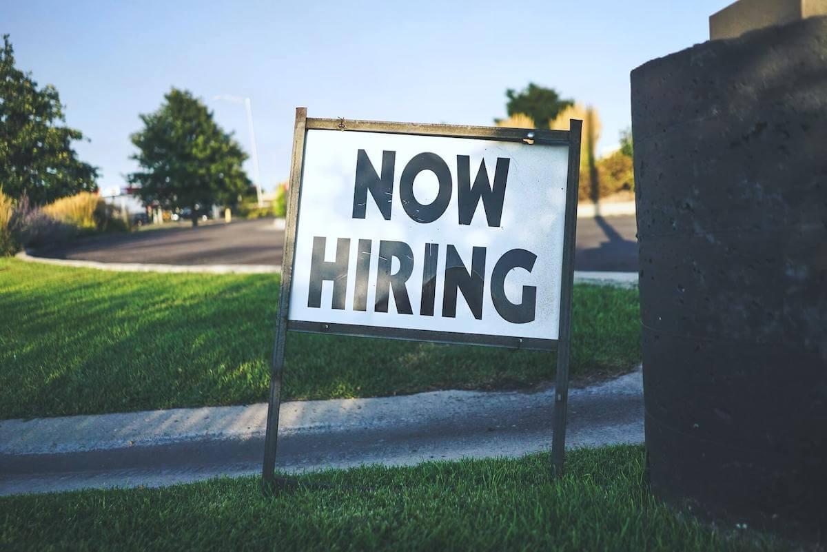 now hiring sign on grass field near street hiring for nursing jobs