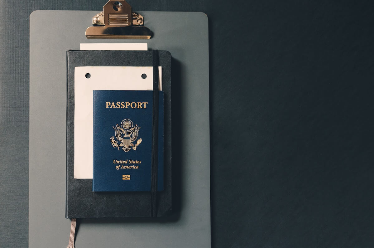 US passport on clipboard on desk travel nurse requirements traveling