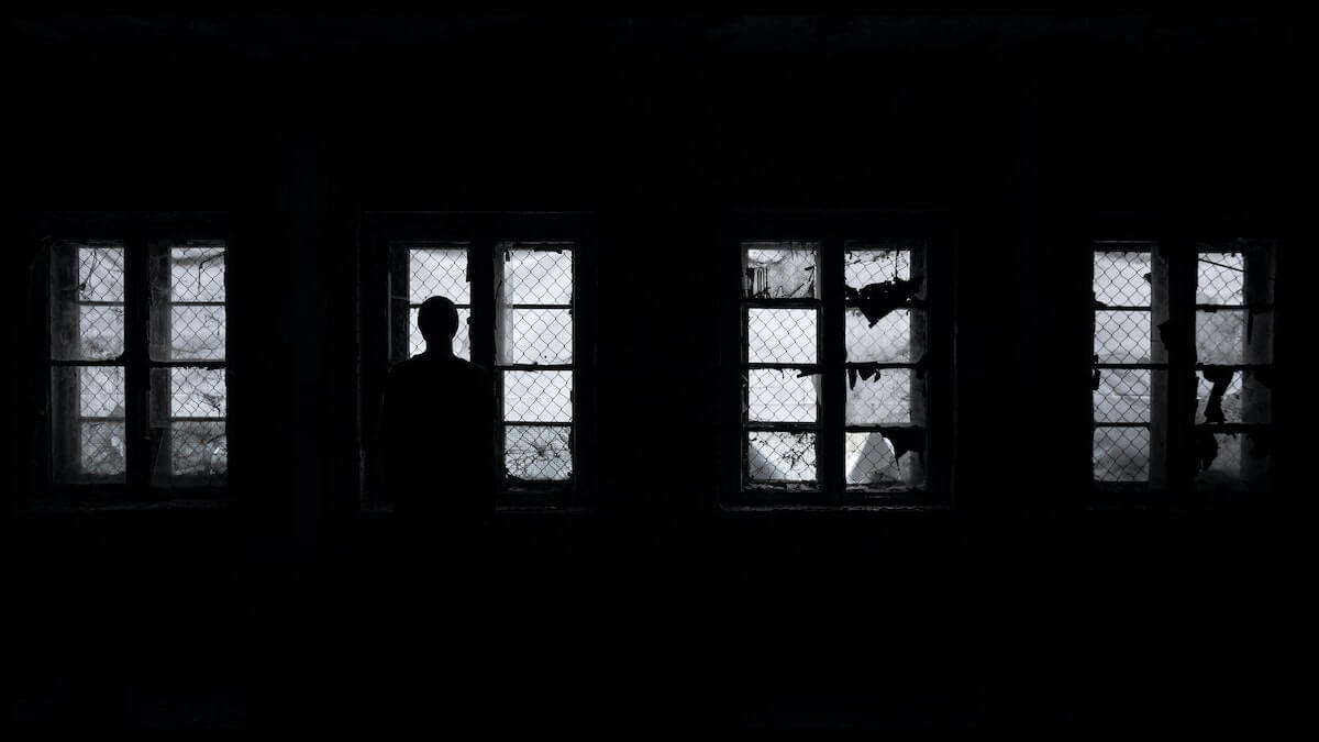 man standing in front of windows in dark room scary nursing stories