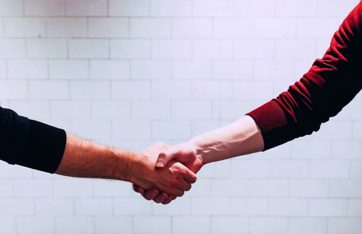 two men shaking hands in front of white wall travel nurse contract