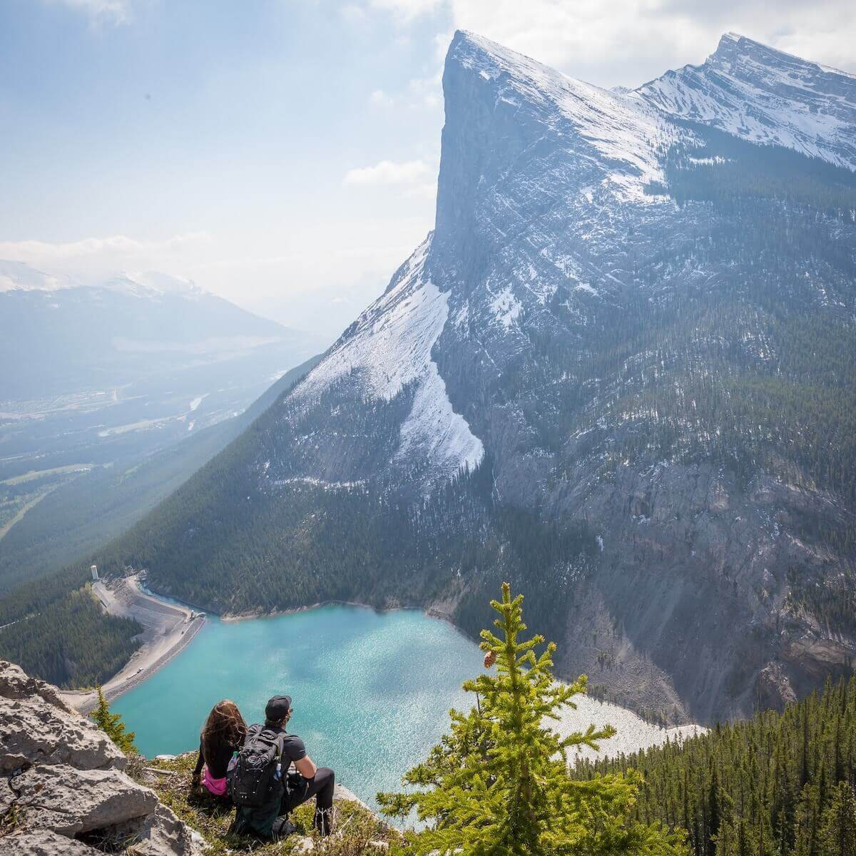 two people sitting on edge of cliff of mountain landscape travel nurses